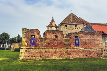 FAGARAS, ROMANIA - JUNE 4, 2015: The fortification walls and towers of the Fagaras fortress, built around 1310, one of the largest and best preserved feudal castles in Eastern Europe.