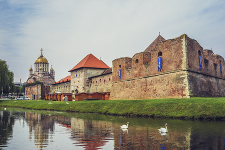 fagaras: FAGARAS, ROMANIA - JUNE 4, 2015: Fagaras fortress, built around 1310, surrounded by a wide defensive ditch filled with water, one of the largest and best preserved feudal castles in Eastern Europe. Editorial