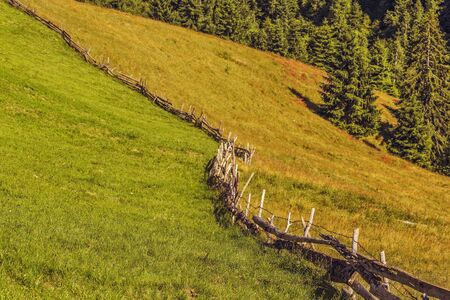 meandering: Summer countryside landscape with meandering traditional Romanian wooden fence and grasslands uphill in Pestera village, Brasov county, Romania. Stock Photo