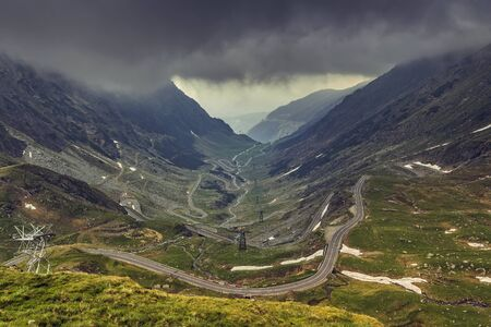 highway: Stormy mountain landscape with famous sinuous Transfagarasan road in Fagaras mountains, Romania. Stock Photo