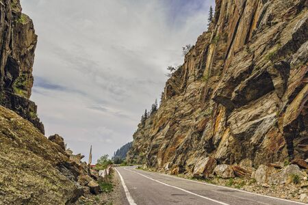 Sunny mountain landscape with Transfagarasan road meandering along high rocky steep cliffs in Fagaras mountains, Romania. Stock Photo