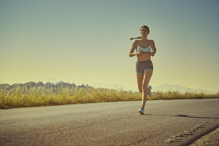 early morning: Active sporty woman in summer sportswear running, sprinting on a road at sunrise or sunset. Health care, body care, healthy lifestyle, willingness concept. Toned color edit.