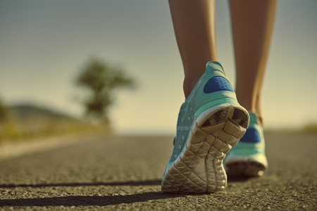 training shoes: Closeup of athlete female feet in running shoes jogging on the road early in the morning. Healthy lifestyle. Stock Photo