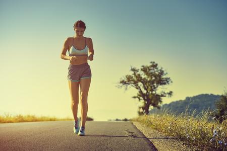 Mujer hermosa del ajuste en pantalones cortos del deporte que se ejecuta en una carretera al amanecer o al atardecer. Concepto de estilo de vida saludable. Virada con Instagram cálido como filtro.