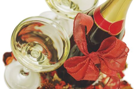 tinted glasses: Closeup of a champagne bottle with red Christmas bow, two filled glasses and decoration over white background. Tinted, matte  colors.