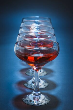 crystal glass: Row of aligned stemmed glasses filled with red wine over blue background. Shallow depth of field.