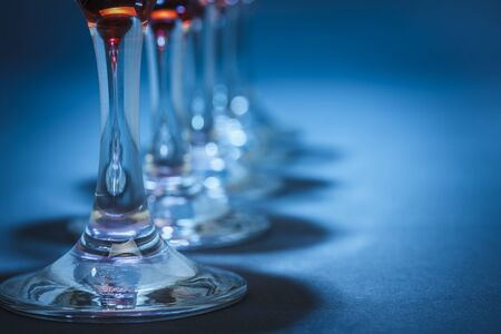 aligned: Closeup of aligned wine glasses stems over blue background. Shallow depth of field.