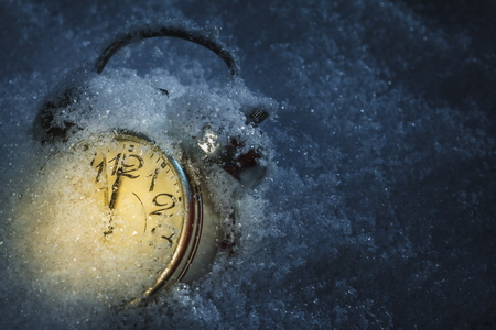Winter is coming. Frozen retro alarm clock pointing twelve o'clock, midnight, covered by snow, dark background with copy space. Shallow depth of field.
