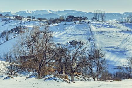 uphill: Sunny winter rural landscape uphill in old traditional Magura village, Brasov county, Romania. Stock Photo