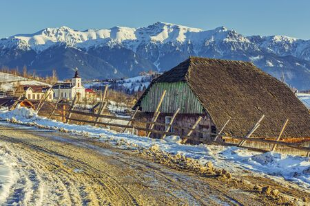 thawed: Rural winter scenery with old traditional wooden cottage and thawed snowy country road in Magura village, Romania. Stock Photo