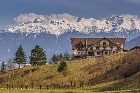 touristic: Picturesque mountain landscape with modern chalet and snowy Bucegi mountains in spring, Romania. Scenic touristic vacation destinations. Stock Photo