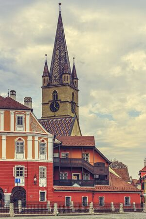 turrets: SIBIU, ROMANIA - 11 NOVEMBER, 2015: The 73.34 m high steeple with clock and four turrets of the Evangelic Church, the landmark of the city, built in 1530 in the Huet Square in Sibiu, Romania.