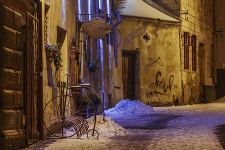 bike parking: BRASOV, ROMANIA - 01 DECEMBER, 2014: Wintry night view of an empty backstreet with vintage bike parking rack in the historic center of Brasov, the 7th largest city and the most visited in Romania. Editorial