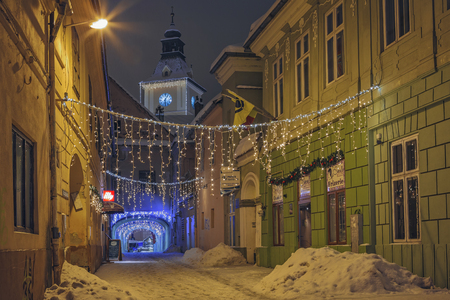 backstreet: BRASOV, ROMANIA - 6 JANUARY, 2015: Winter night scene of an empty snowy backstreet decorated with festive traditional Christmas lights in historic center of Brasov, the 7th largest city in Romania.