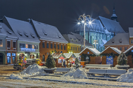 BRASOV, ROMANIA - 6 JANUARY, 2015: Winter night cityscape with traditional Christmas fair in the snowy Council Square in the historic center of Brasov city.