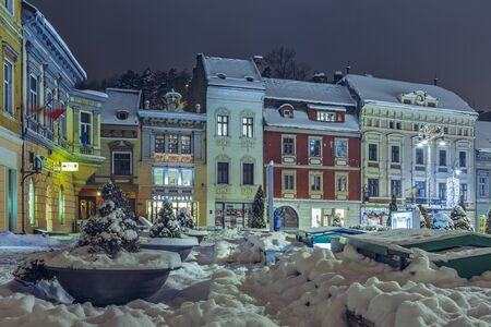 BRASOV, ROMANIA - 6 JANUARY, 2015: Winter nightfall city view with snowy Council Square in the historic center of Brasov city on Christmas holidays.