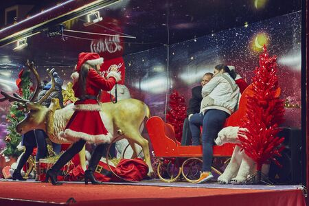 say cheese: BRASOV, ROMANIA - DECEMBER 10, 2015: Santa Claus helper lady takes a snapshot of a merry couple posing in a decorative red sleigh inside the Red Coca-Cola truck trailer in the Council Square.