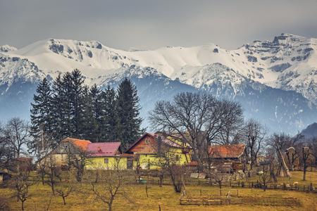 sheepfold: Spring rural landscape with snowy Bucegi mountains and traditional Romanian houses and farm in Predelut village, near Bran, Transylvania region, Romania.