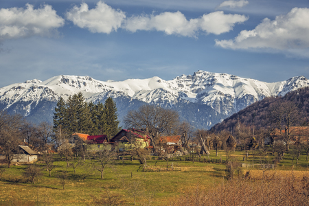 sunny: Spring sunny countryside landscape with snowy Bucegi mountains and traditional Romanian houses and farmland in Predelut village, near Bran, Transylvania region, Romania. Stock Photo