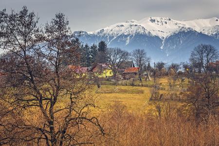 sheepfold: Spring rural landscape with snowy Bucegi mountains and traditional Romanian village in Predelut village, near Bran, Transylvania region, Romania. Stock Photo