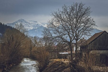 riverside county: Springtime rural scenery with riverside Romanian traditional village and snowy Bucegi mountains, near Rasnov town, Brasov, county, Transylvania region, Romania.