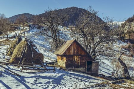sheepfold: Rural scene with traditional Romanian wooden stable and haystacks, on a sunny spring day with melting snow, uphill in Magura village, Brasov county, Transylvania region, Romania. Stock Photo