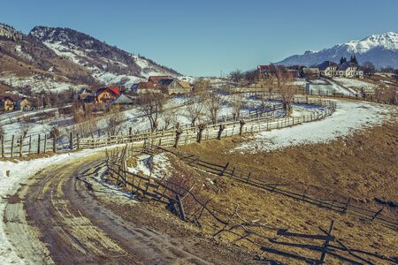 thawed: Serene spring landscape with thawed country road meandering uphill in Magura village, Transylvania region, Romania. Spring thaws season. Hike destinations.