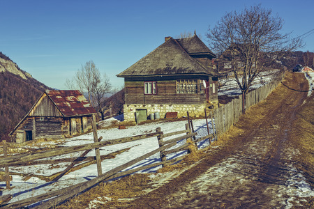 thawed: Spring landscape with rustic Romanian wooden house and barn and thawed country lane uphill in Magura village, Transylvania region, Romania. Spring thaws season. Hike destinations. Stock Photo
