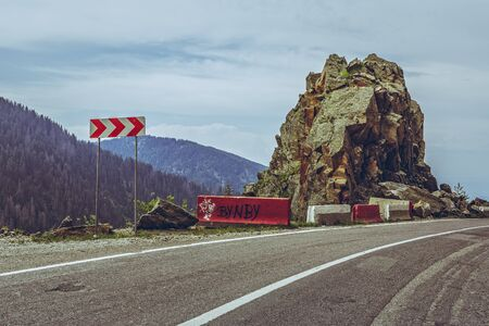 sinuous: Roadside red and white triple chevron sign warning for dangerous road turn on sinuous Transfagarasan highway, Romania.