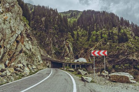 dangerous road: Picturesque mountain landscape with roadside triple chevron sign warning for dangerous road turn on sinuous Transfagarasan highway, Romania.