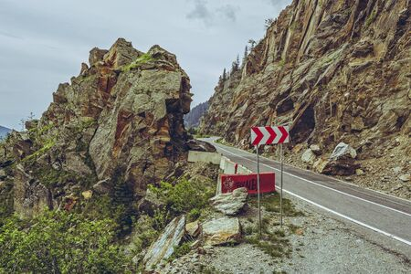 steep cliff sign: Picturesque mountain landscape with roadside red and white triple chevron sign warning for dangerous road turn on sinuous Transfagarasan highway, Romania.