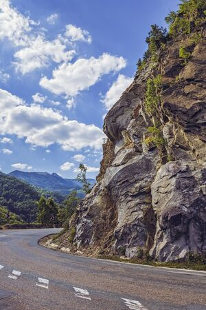county side: Sunny summer view with steep rocky cliff on the side of a road crossing the Siriu mountains in Buzau county, Romania. Stock Photo