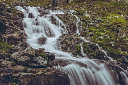 upstream: Majestic mountain stream waterfall nearby the famous Transfagarasan road in Fagaras mountains, Romania. Long exposure motion blur.