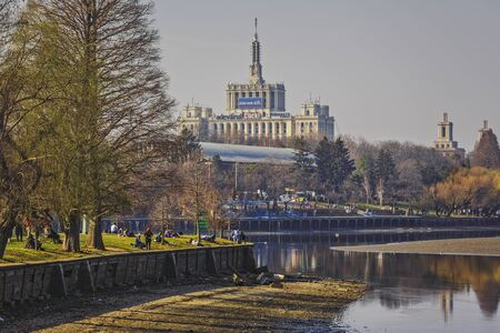 edifice: Bucharest, Romania - March 09, 2013: People relax on the bank of the lake in Herastrau park. House of the Free Press in the background, the tallest edifice in the city between 1956 and 2007.