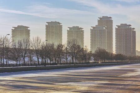 apartment blocks: Picturesque morning scenery with modern high rise block of flats near frozen Dambovita river, in south-eastern Bucharest, Romania. High rise apartment blocks, tower blocks, real estate development.