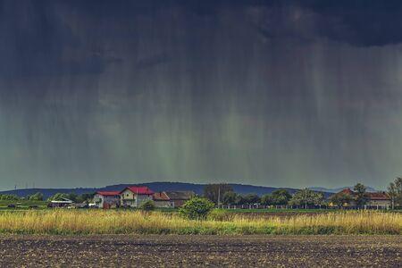 rain weather: Cloudburst over a village and farmlands during spring in Transylvania region, Romania.