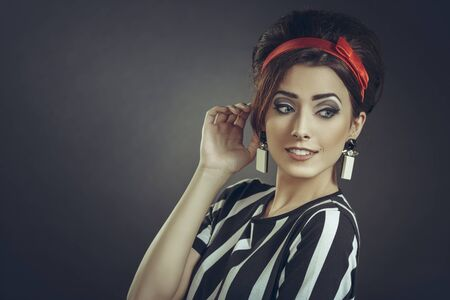 rumors: Beautiful smiling woman with hand to ear, wearing striped apparel, red headband and retro updo hairstyle, eavesdrops on fashion rumors, news or trends gossips, over dark background with copy space. Stock Photo
