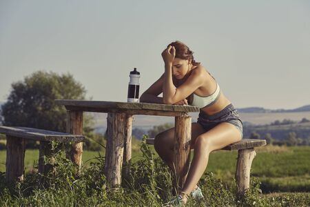 feeble: Exhausted female runner with hand on head resting on a rustic wooden bench. Pretty young woman having a headache from dehydration or overtraining. Young sporty lady having a bad training day. Stock Photo