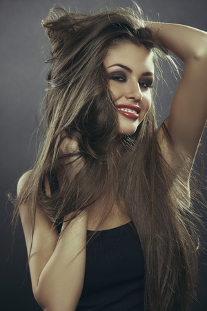 flirtatious: Portrait of attractive sensual flirtatious young woman playing with her hands through her brown long silky hair with fluttering strands. Hair health, hair freshness, hair care.