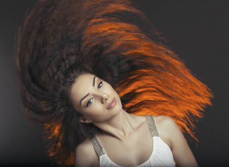 tossing: Beautiful young lady tossing sideways her rich long hair, backlit over dark background. Hair health, hairstyle, hair care.