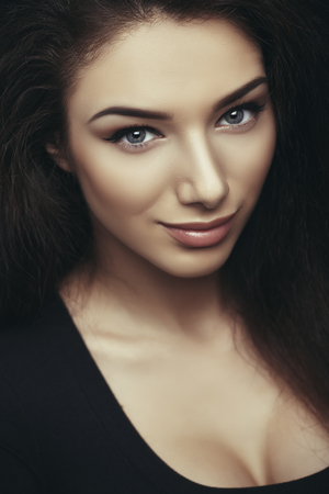 Close portrait of alluring brunette young woman with blue eyes, perfect healthy skin and black low cut blouse, looking at camera.