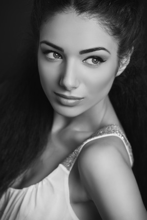 decolletage: Portrait of attractive brunette young woman with blue eyes, healthy skin, looking sideways. Black and white.