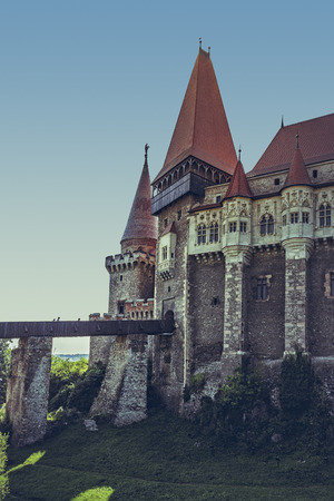drawbridge: Hunedoara, Romania - July 23, 2016: Medieval Corvin Castle with long wooden drawbridge sustained by four massive stony piers, built in Gothic-Renaissance style in the 14th century.