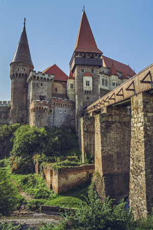 sustained: Hunedoara, Romania - July 23, 2016:  Legendary Medieval Corvin Castle with long wooden drawbridge sustained by four massive stony piers, built in Gothic-Renaissance style in the 14th century.