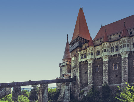 sustained: Hunedoara, Romania - July 23, 2016: Medieval Corvin Castle with long wooden drawbridge sustained by four massive stony piers, built in Gothic-Renaissance style in the 14th century.