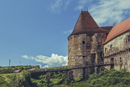 bastion: Hunedoara, Romania - July 23, 2016: Wooden bridge over a large defense moat at the Old Gate Tower which is the old entrance to the Corvin Castle, one of the most popular tourist sites in Romania.