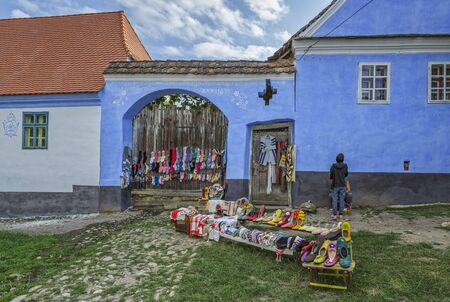 Viscri, Romania - July 21, 2016: Handmade wool and felt clothes designed by the locals, exhibited in front of their houses on a narrow street of the Saxon landmark village in Transylvania.