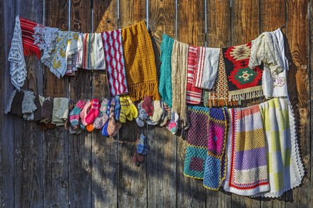 Colorful handcrafted pieces of fabric hanged for trade on a wooden fence in Viscri village, Transylvania, Romania.