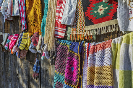 Closeup of colored homemade pieces of fabric hanged for trade on a wooden fence in Viscri village,Transylvania, Romania. Stock Photo
