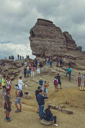 resemblance: Bucegi Mountains, Romania - August 6, 2016: Thousands of people hike to Sphinx (Romanian: Sfinxul), the ancestral megalith with human face resemblance situated at 2,216 m altitude in Bucegi Mountains.